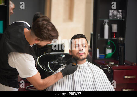 Professional male hairdresser in black gloves grooming man's beard with brush. Handsome man with stylish haircut sitting and looking away. Concept of barbershop and wellness. - Stock Photo