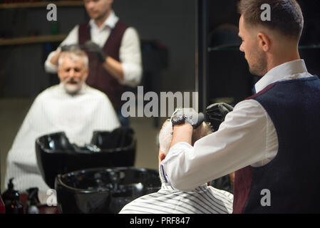 Professional barber in white shirt, vest and black gloves grooming and styling haircut of his client. Reflection in mirror of man and master. Concept of procedures in barbershop and hair care. - Stock Photo