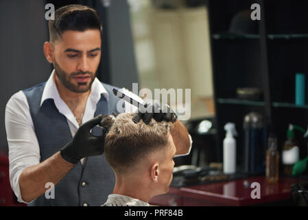 Concentrated barber looking at client and trimming haircut of young man. Bearded male hairdresser holding trimmer and comb in hands. Handsome master wearing black gloves. - Stock Photo