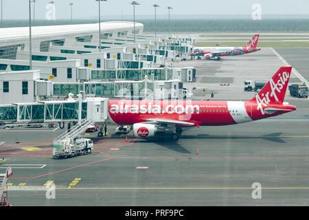 Malaysia, Kuala Lumpur International Airport, 04-03-2018: Passengers using jet bridge to boarding in airplane by Airasia airline. Airport daily routin - Stock Photo