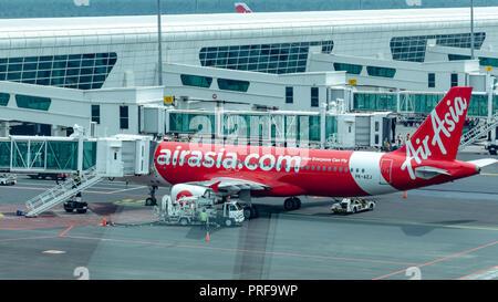Malaysia, Kuala Lumpur International Airport, 04-03-2018:  Airplane by company Airasia preparing for departure,  jet bridge with passengers, refueling - Stock Photo