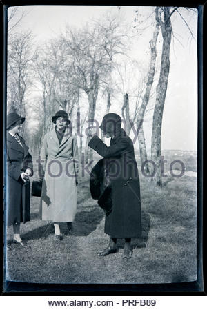 women standing and talking in a rural landscape with a trees lined path France circa 1920s - Stock Photo