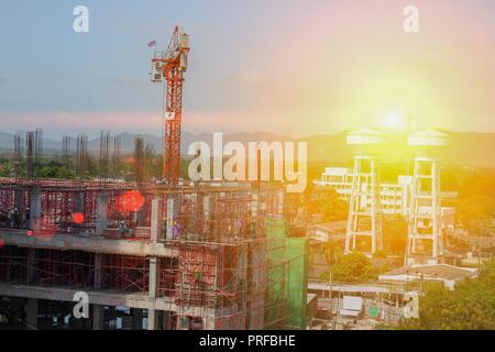 Construction and renovation of tall building  under in scaffolding in Thailand  with sunset light tone. - Stock Photo