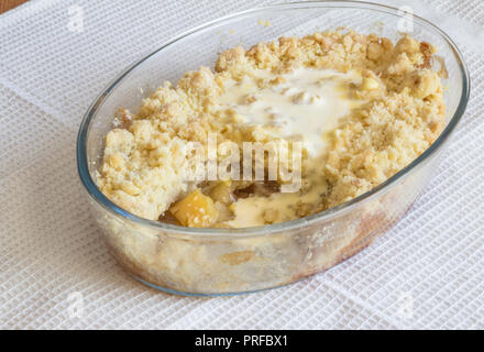 Apple crumble in glass dish with runny cream topping on white cloth - Stock Photo