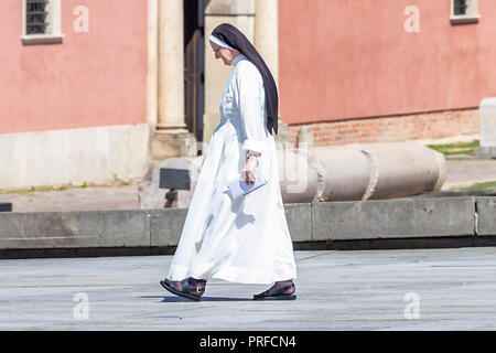 Warsaw, Poland May 31, 2018: The nun walks through plac Zamkowy (Zamkowy square) in front of The Royal Castle of Warsaw, Poland - Stock Photo
