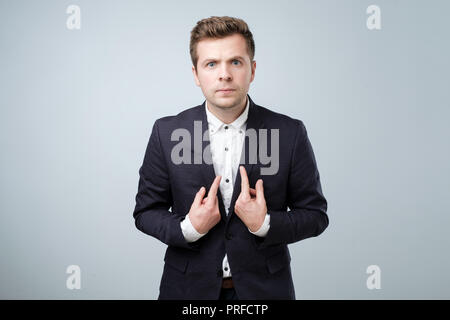 Young european man in suit pointing at himself, making excuses or verbally defending, having perplexed and puzzled look. - Stock Photo
