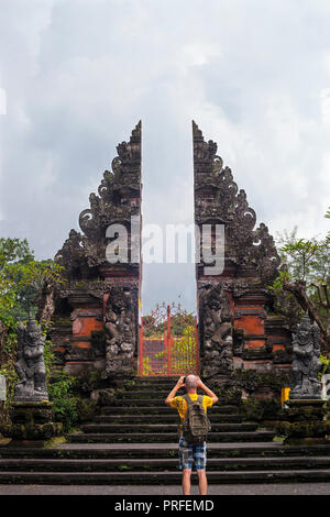 Tourist with backpacker making photo by phone of traditional entrance to Hindu temple in  Ubud, Bali - Stock Photo