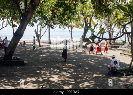 Bali, Indonesia - 07 March 2018: Balinese people in traditional clothes walking near blue ocean - Stock Photo
