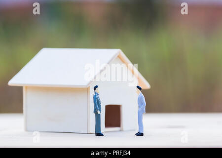 Home bargain, real estate, loan, house lender reverse mortgage concept : Two Miniature businessmen bargain front small residence on wooden table and b