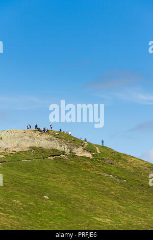 Walkers enjoy the experience of reaching the summit of  Cat Bells (451 metres) near Keswick, Cumbria. - Stock Photo