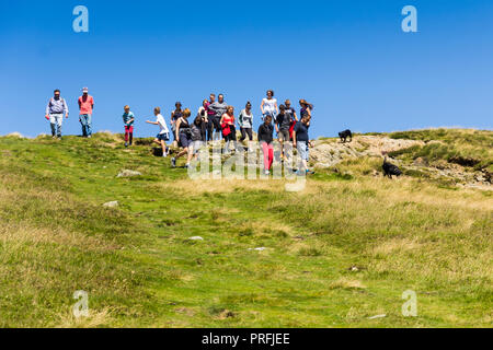 A group of young people and other walkers on the footpath leading south from the summit of  Cat Bells (451 metres) near Keswick, Cumbria. - Stock Photo