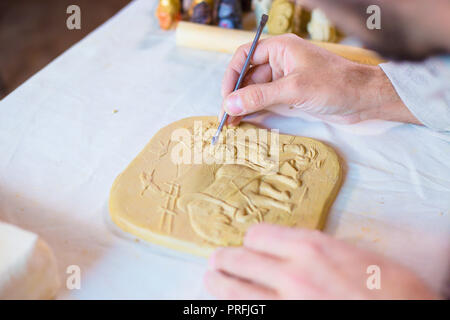 Professional male potter making clay stamp picture. Handwork, crafting and traditional arts concept - Stock Photo