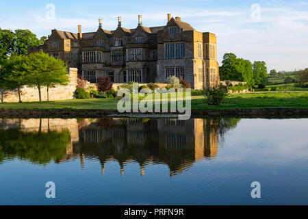 Broughton Castle, near Banbury, home of the Fiennes family in golden evening light with reflections in the still water of the moat. Open to the public - Stock Photo