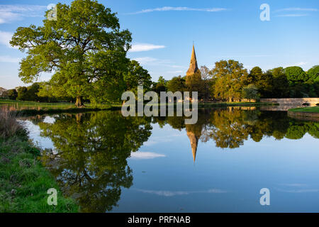 Broughton Castle and church, near Banbury, home of the Fiennes family in golden evening light with reflections in the still water of the moat. - Stock Photo