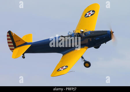 Fairchild PT-19 Cornell plane flying at an airshow. Second World War primary trainer for the United States Army Air Force with old style markings - Stock Photo