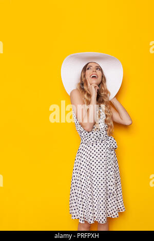 Beautiful young woman in white dotted summer dress and sun hat is smiling, holding finger on chin and looking up at copy space. Three quarter length s - Stock Photo