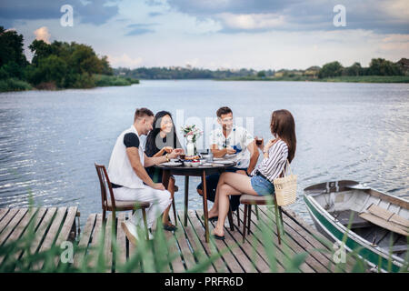 Group of happy friends gathering to having dinner together at summer picnic. Food, eating and fun concept - Stock Photo