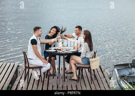 Cheers! Group of friends enjoying outdoor picnic in river pier. Friendship, food and fun concept - Stock Photo