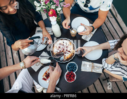 Enjoying meal with friends. Top view of group of people having breakfast together while sitting at table. eating and family concept - Stock Photo