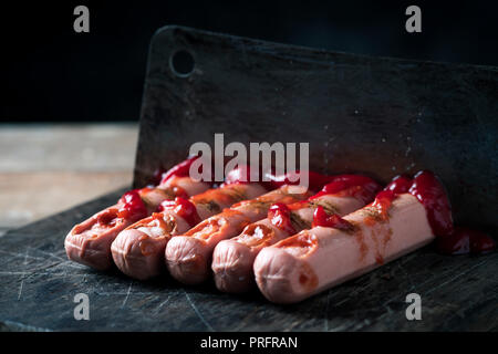 closeup of some scary hotdogs in the shape of bloody fingers cut with a cleaver, on a rustic chopping board - Stock Photo