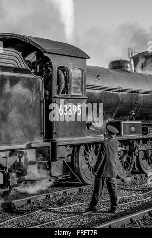 Black & white portrait close up of UK steam locomotive on the track at heritage railway station. Train guard speaks with steam train crew in cab. - Stock Photo