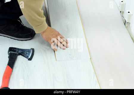Renovation of an apartment, man laying laminate flooring in the room. - Stock Photo