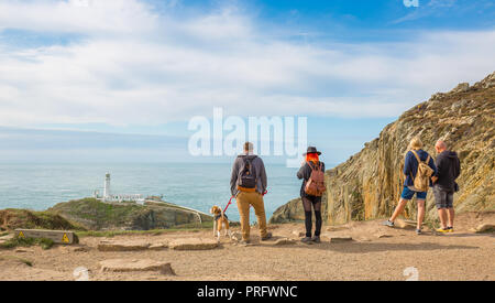 Rear view of people stood in sunshine (at RSPB South Stack Cliffs) staring at landscape: looking out to sea at South Stack Lighthouse, Anglesey, UK. - Stock Photo