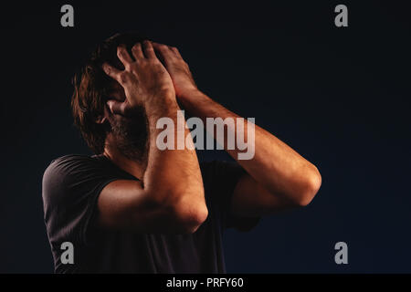 Man is crying in despair, hands covering face, low key portrait - Stock Photo