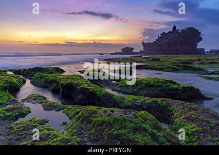 Sunset over Tanah Lot temple in Canggu, Bali, Indonesia. - Stock Photo