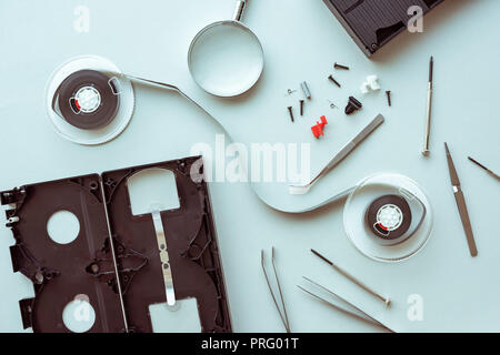Flat lay vhs video cassette parts on pastel blue background, top view of retro technology and media concept - Stock Photo