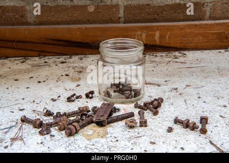 Jar of rusty bolts, nuts, hinges and washers on a workshop bench. - Stock Photo