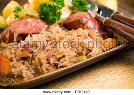 Bavarian food prepared in the spirit of Oktoberfest and the fall season: kielbasa (sausage), boiled, parsley potatoes, sauerkraut baked in savory sau - Stock Photo
