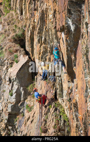 Portrait capture, three men enjoying challenge of extreme sport activity: abseiling and rock climbing on rockface at South Stack Cliffs, Anglesey, UK. - Stock Photo