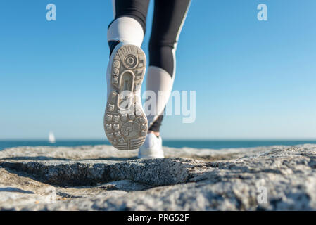 close up of the sole of a running shoe, cross country along the seashore and rocks. - Stock Photo
