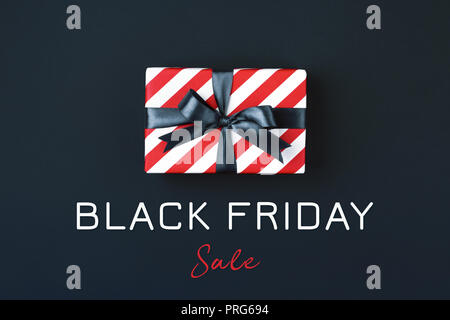 Gift box wrapped in red striped paper and tied with black bow on black background. Black friday concept, top view.