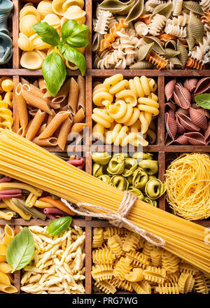 Assorted colorful italian pasta in wooden box - Stock Photo