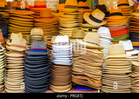 Piles of straw hats on display at Camden Market in London - Stock Photo