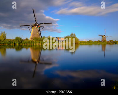 Autumn golden hour light on the windmills, canals and polders of Kinderdijk, near Rotterdam, Netherlands - Stock Photo