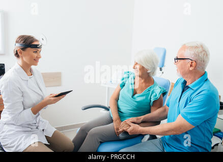 ENT Doctor talking with senior patients in doctors office - Stock Photo
