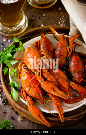 Boiled Crawfish and Fresh Beer in Beakers on a wooden table. Appetizer protein. - Stock Photo