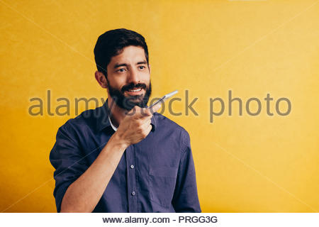 Leisure, technology, communication and people concept - young man using voice command recorder or calling on smartphone - Stock Photo