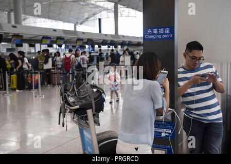 Chek Lap Kok island, Hong Kong. 28th Sep, 2018. Passengers are seen charging their smart phones at Hong Kong's airport terminal 1. Credit: Miguel Candela/SOPA Images/ZUMA Wire/Alamy Live News - Stock Photo