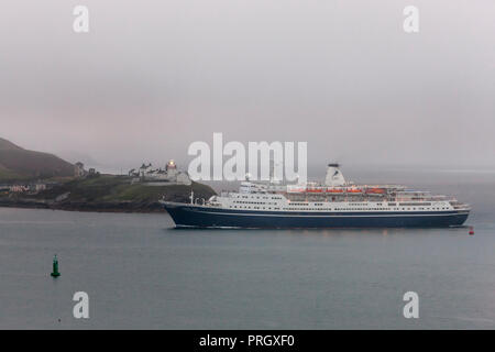 Roches Point, Cork, Ireland. 03rd October, 2018. Cruise ship Marco Polo passing the Roches Point Lighthose as fog begins to lift in Cork Harbour, Ireland. Credit: David Creedon/Alamy Live News - Stock Photo