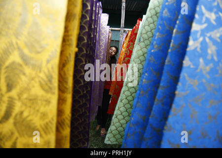 Kathmandu, Nepal. 3rd Oct, 2018. A Nepalese woman dries screen-printed decorative paper made of Lokta raw materials at a factory in Lalitpur, Nepal on Wednesday, October 3, 2018. Lokta is a Daphne plant acquired from the bark of the Daphne bush, which grows abundantly in the Himalayan foothills at high altitudes. Credit: Skanda Gautam/ZUMA Wire/Alamy Live News - Stock Photo