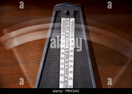 Close up of a vintage metronome with swinging pendulum - Stock Photo