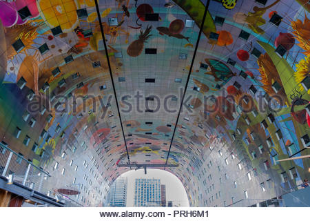 Characteristic and colourful painted ceiling inside the market hall in Rotterdam. In the arch building are residential homes and offices and a market  - Stock Photo