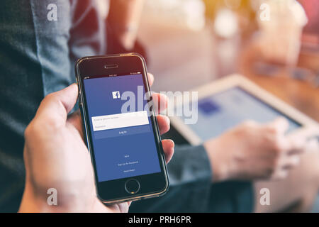 Facebook App on iPhone with people using tablet background closeup male hand hold social network on smart device concept.23 September 2018,Bangkok Tha - Stock Photo