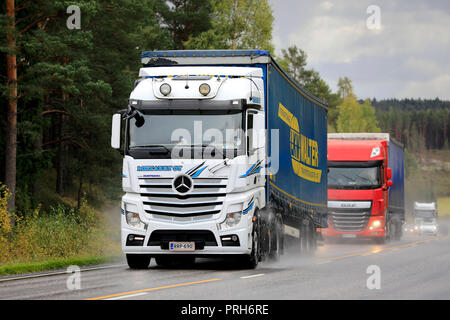Salo, Finland - September 28, 2018: White Mercedes-Benz and red DAF freight semi truck traffic on wet road on rainy autumn day in South of Finland. - Stock Photo