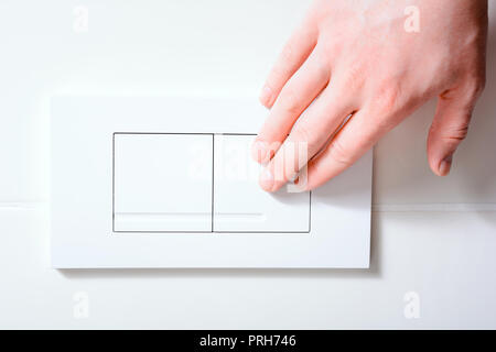 Male Hand Pressing Right Plate Of A Dual Flush Toilet For A Small Amount Of Water - Water Saving Concept - Stock Photo