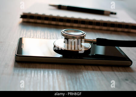 Stethoscope On A Black Smartphone Next To A Notepad And Biro - Fixing A Broken Mobile Phone Concept - Stock Photo